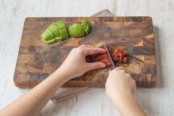 getrocknete Tomaten grob hacken, Avocado in Würfel schneiden