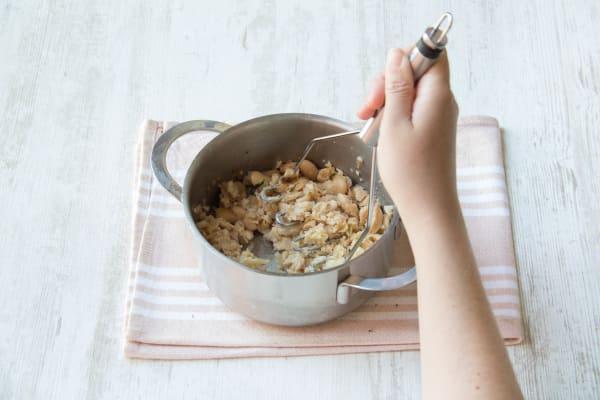 Zutaten mit einem Kartoffelstampfer vermengen