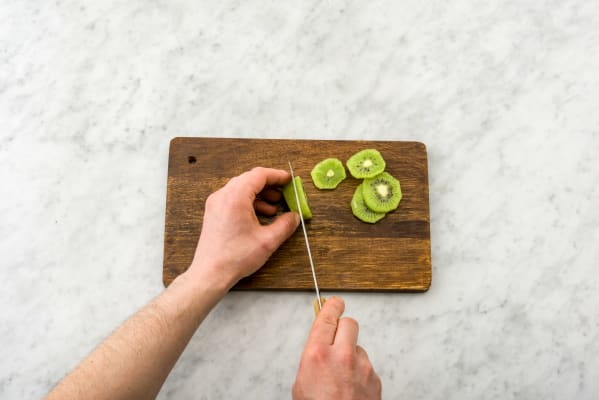 Schil de kiwi en snijd in plakken.