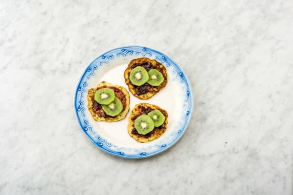 Besmeer met de kersenjam en beleg met de kiwi.