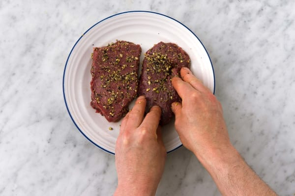 Evenly coat the steaks in the dukkah