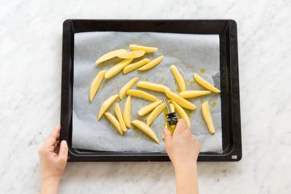 Kartoffelspalten mit Öl vermischen