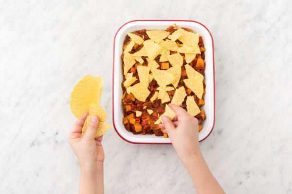 Émiettez les coquilles à tacos au-dessus du plat.