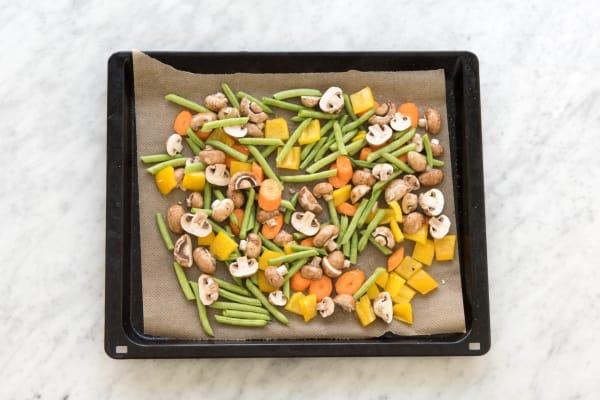 Gemüse auf einem mit Backpapier belegten Backblech verteilen