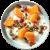 Fromage blanc entier aux fruits orange avec des pistaches et des dattes