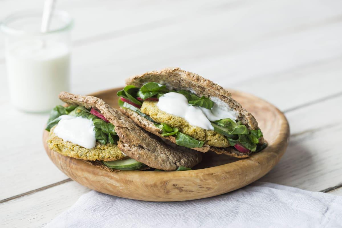 Volkoren pitabrood met falafelburgers, frisse salade en romige yoghurtsaus