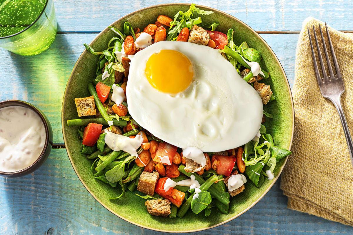 Salade de haricots, croûtons et œuf au plat