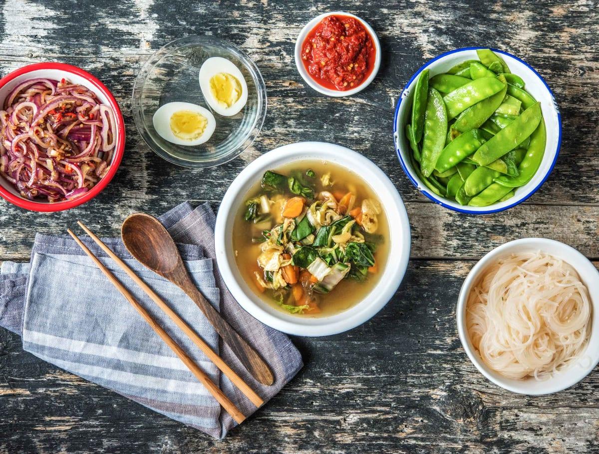 Indonesische soto met een gekookt ei, peultjes en rijstvermicelli