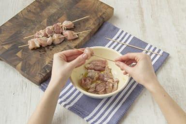 Das vorbereitete Hähnchenfleisch auf die Spieße stecken