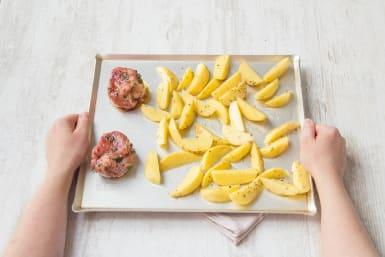 Die marinierten Filets zu den Kartoffeln auf das Backblech legen