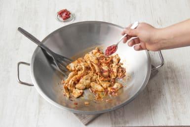 Voeg de tomatenpuree en komijnpoeder bij de kip