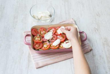 Verdeel de mozzarella over de tomaten