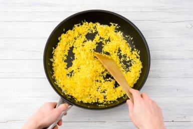 Voeg de rijst toe en bak mee.