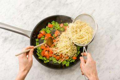 Voeg vervolgens tomaat, noedels, sojasaus en de helft van de pindasaus toe aan de snijbonen.