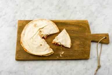Snijd het gevulde platbrood in punten en verdeel over de borden.