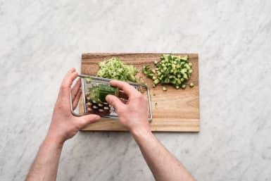 Snijd de komkommer in blokjes en rasp het andere deel.