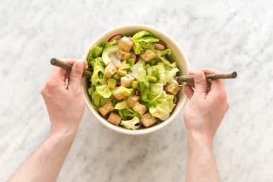 Voeg de dressing toe aan de salade.