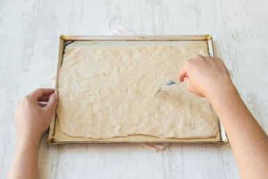 Prick the pizza dough with a fork