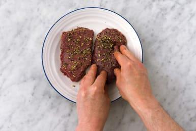 Evenly coat the steaks in the dukkah