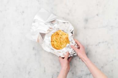 Warm naan and melt butter