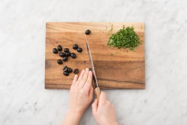 Snijd de koriander fijn en halveer de olijven