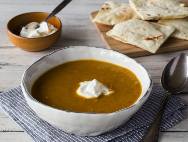 Zoete wortel–linzensoep met crème fraîche en naanbrood